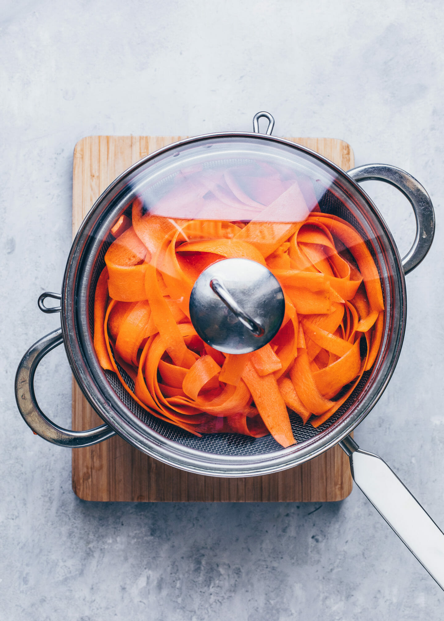 steaming carrot strips in a steamer basket in a pot with water
