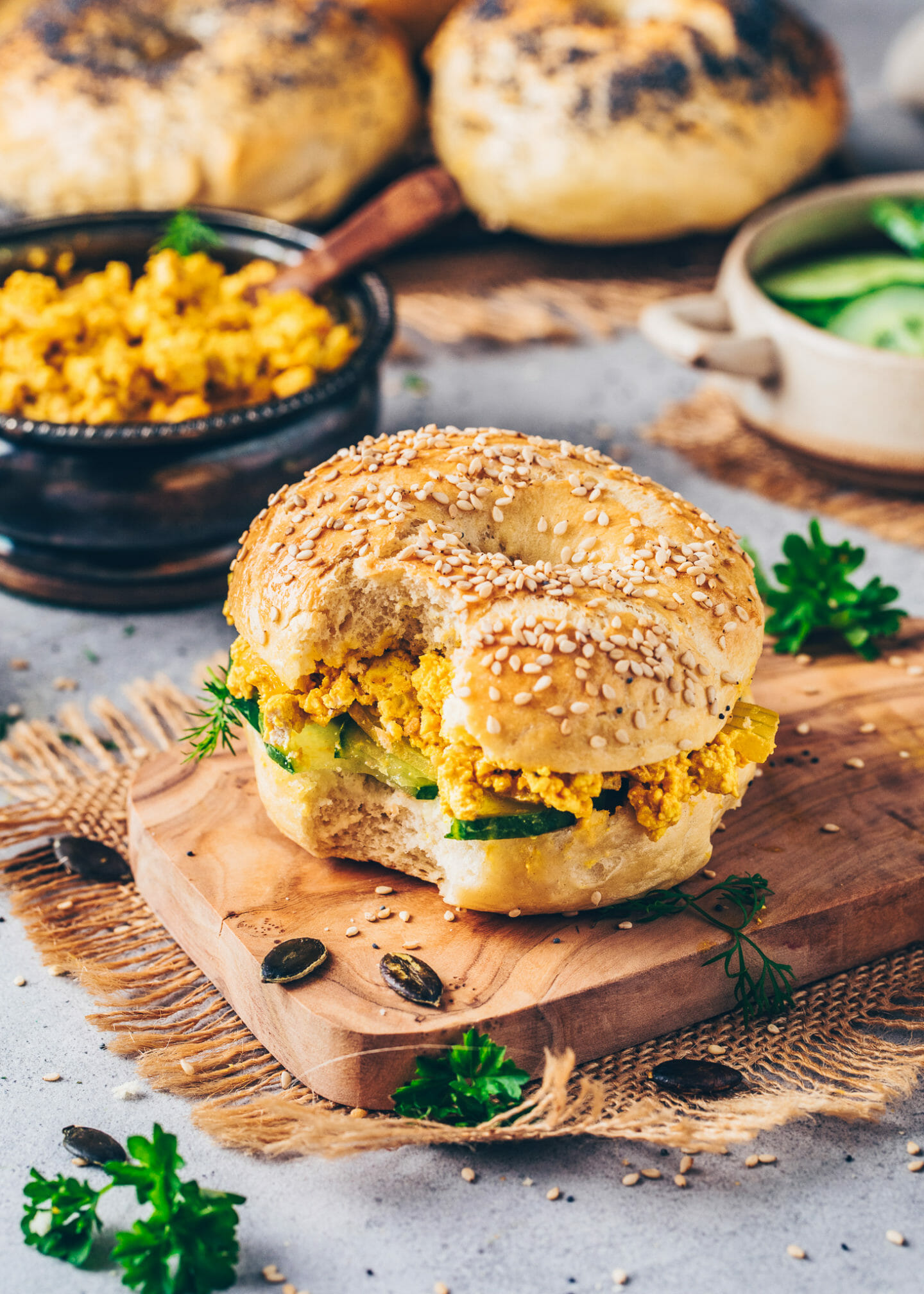 tofu scramble with cucumber and dill on top of bagel