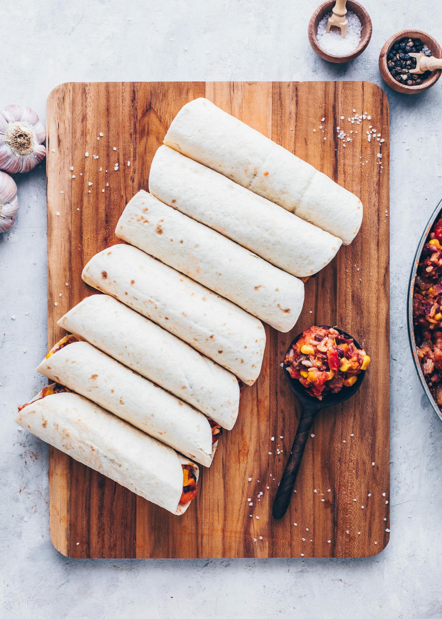 wrapped enchiladas on a chopping board