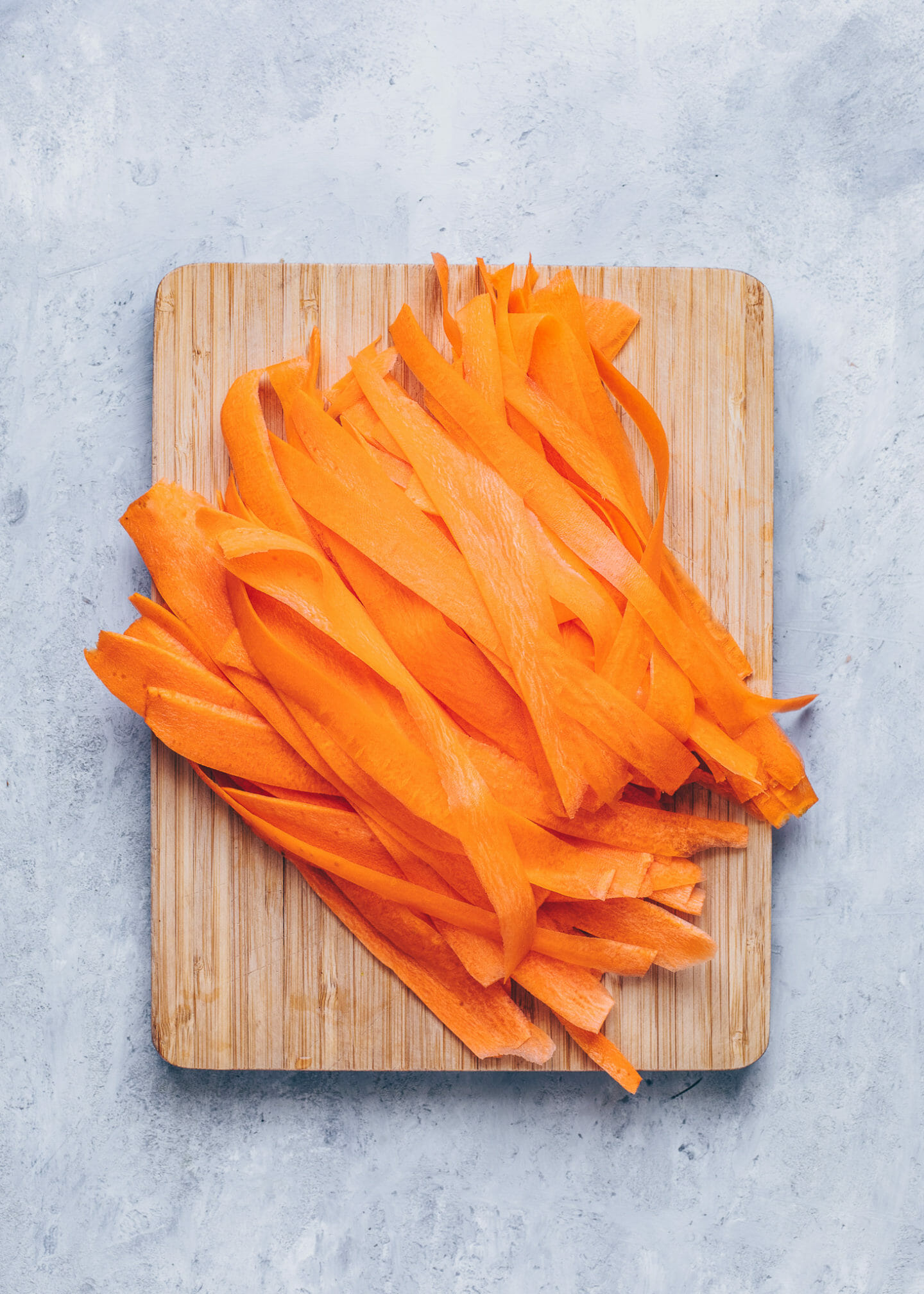 thin carrot ribbons on a chopping board
