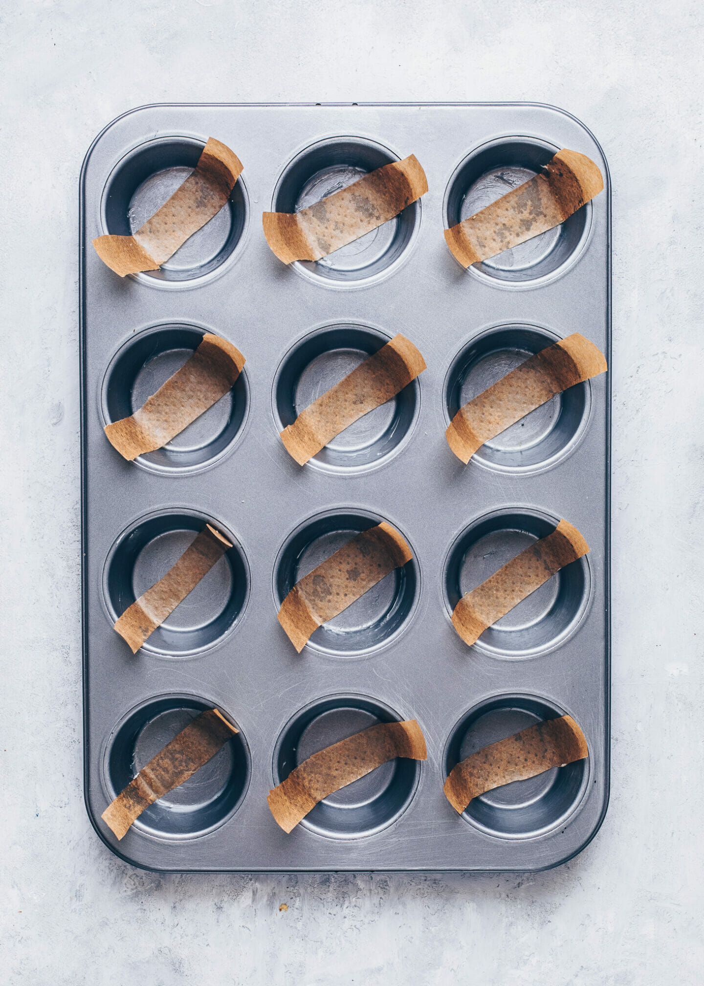 muffin tins lined with parchment paper strips