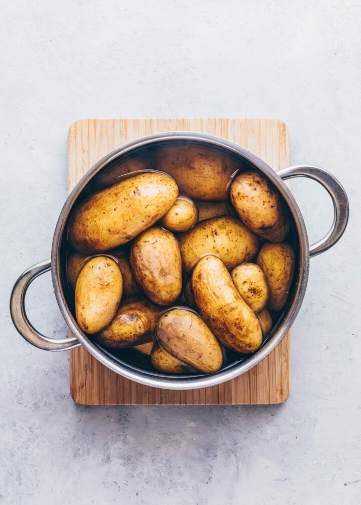 whole potatoes in a pot of salted water