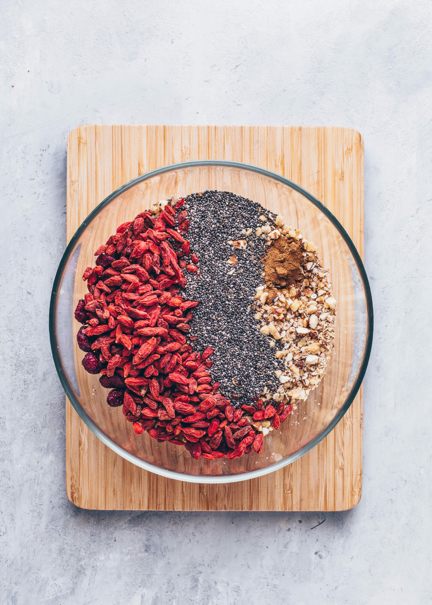 oats, walnuts, almonds, chia seeds, cinnamon, cranberries and goji berries in a bowl for granola