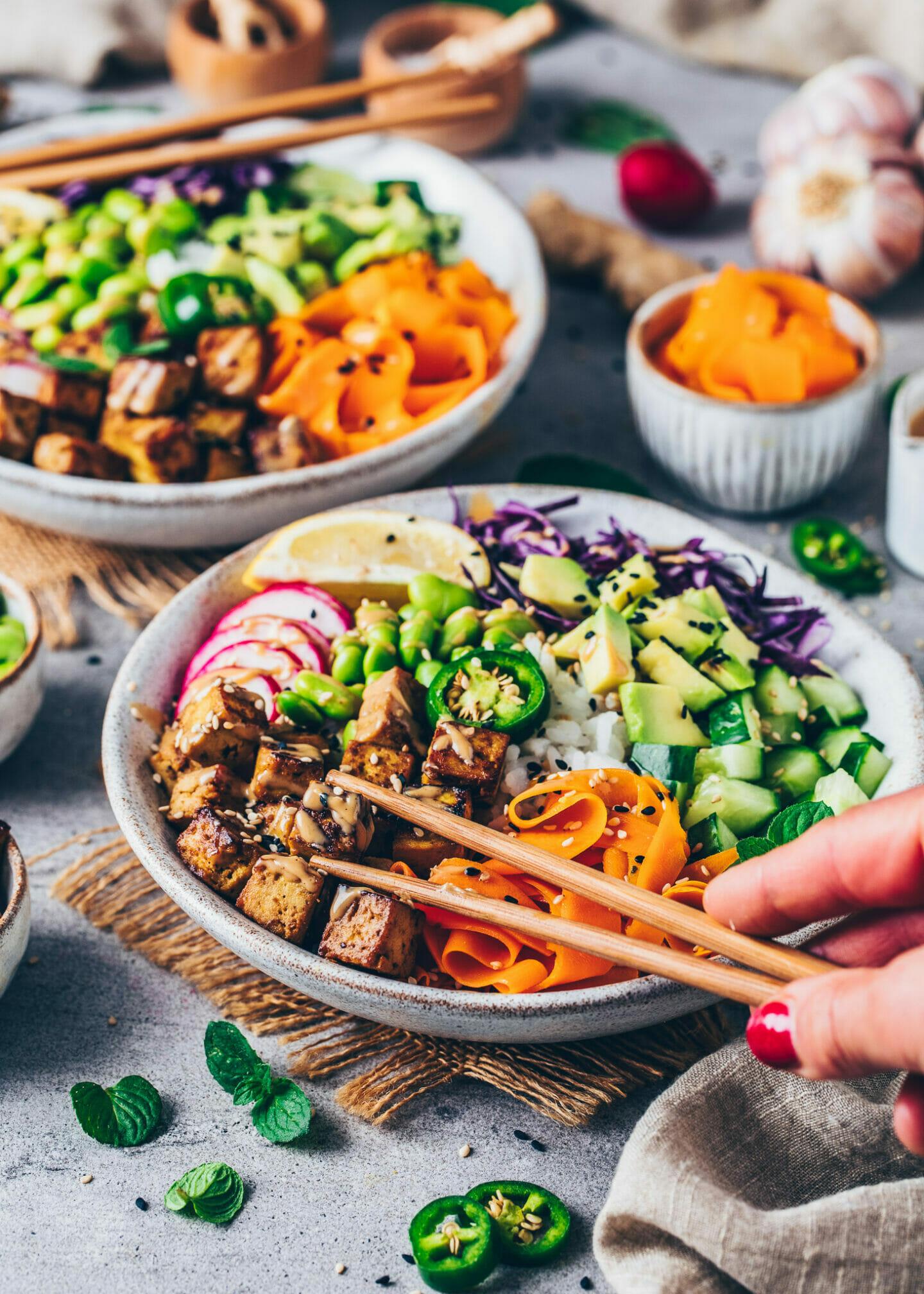 Poke Bowl mit knusprigem Tofu, Radieschen, Karotten, Rotkohl, Gurken, Edamame und Tahini-Sauce