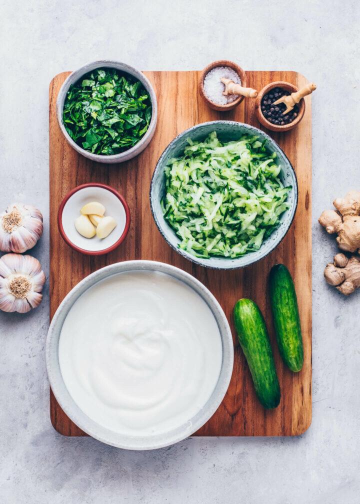 Zutaten für Raita Dip mit Joghurt, Gurke, Knoblauch, Ingwer, Petersilie, Koriander, Minze, Kreuzkümmel, Salz und Pfeffer
