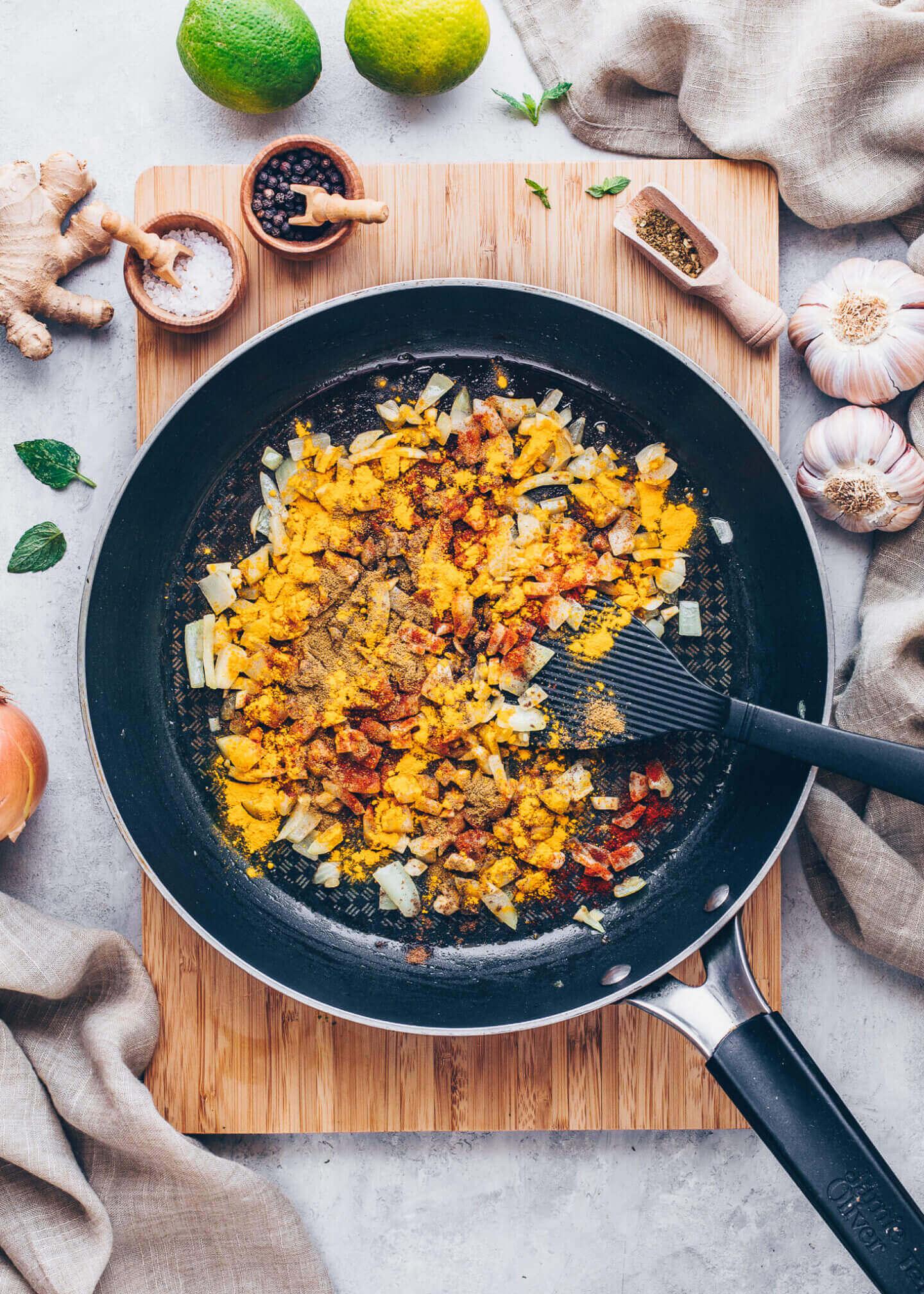 gebratene Zwiebeln, Knoblauch, Ingwer, Garam Masala, Paprikapulver und Kurkuma in einer Pfanne anbraten