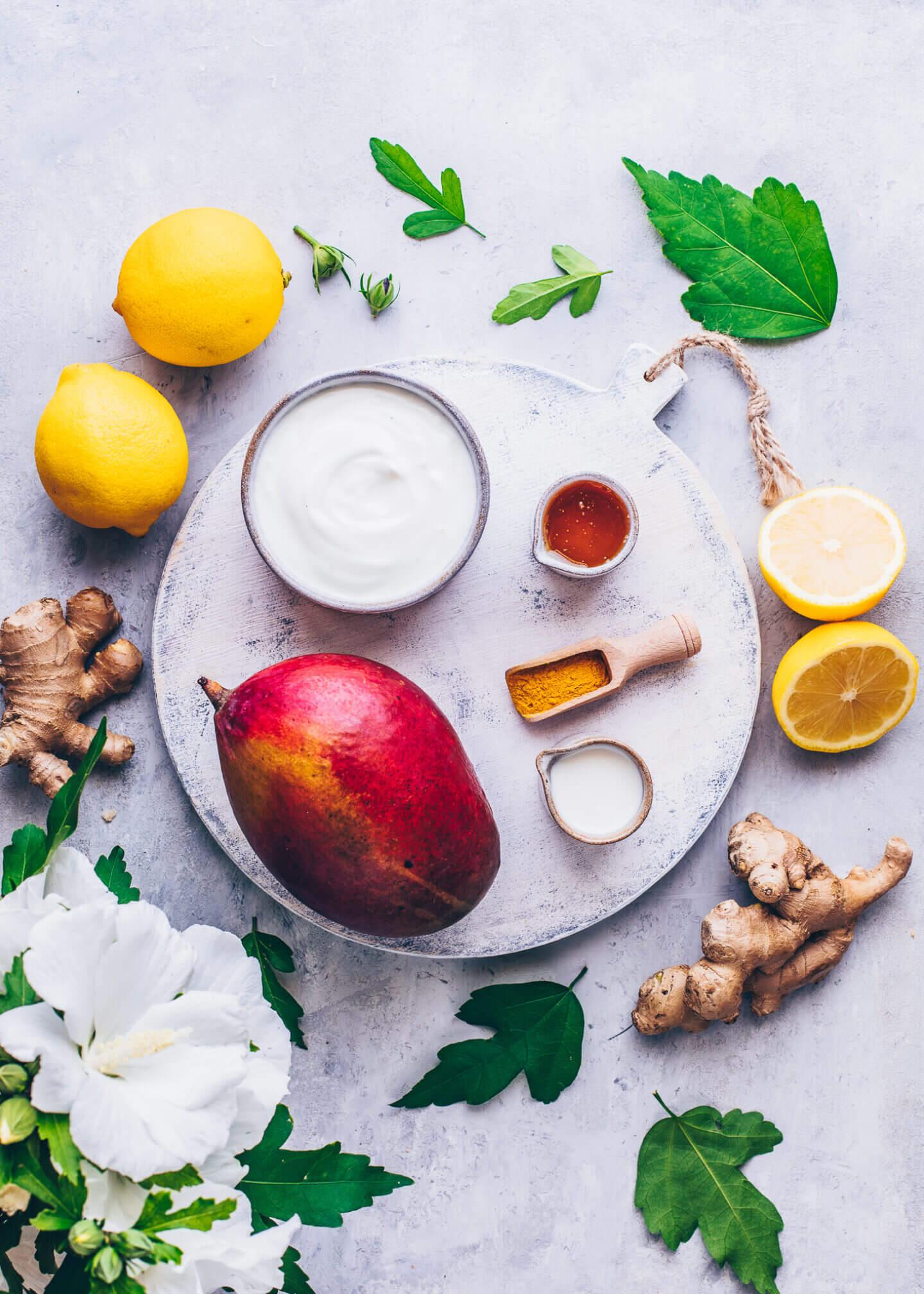 Ingredients for Mango Lassi: mango, vegan yogurt, fresh ginger, agave syrup, lemons, turmeric