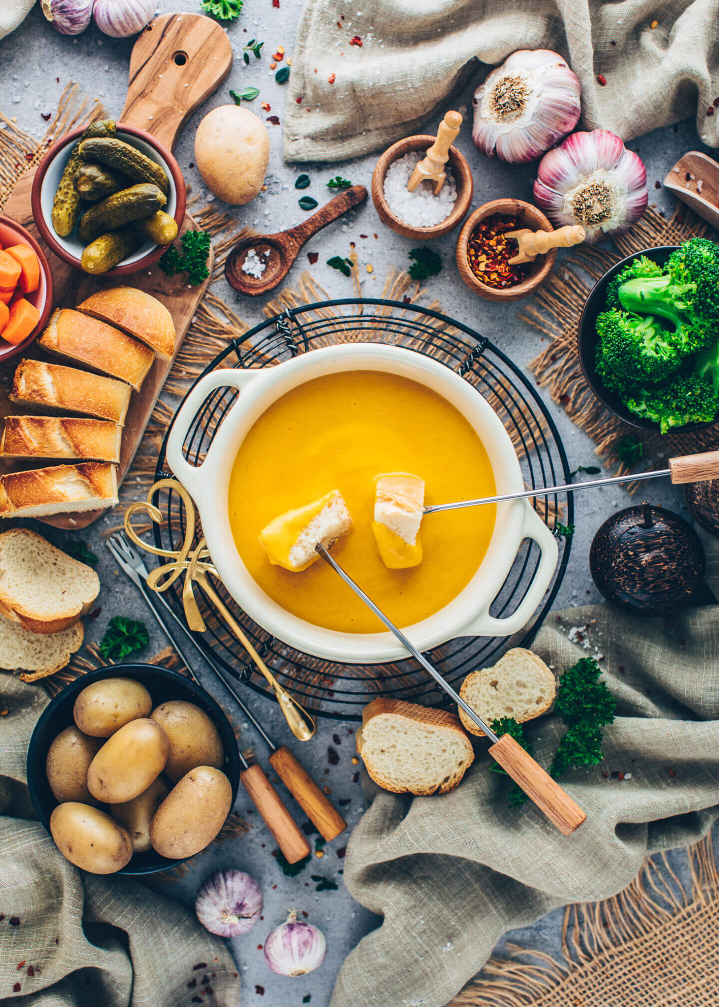 Vegan Cheese Fondue with bread, broccoli, carrots, potatoes, cucumbers, and garlic