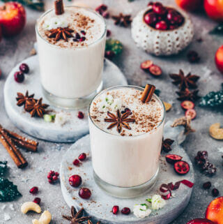 Vegan Eggnog Punch in glasses with cinnamon, pomegranate, star, anise, apples and cranberries