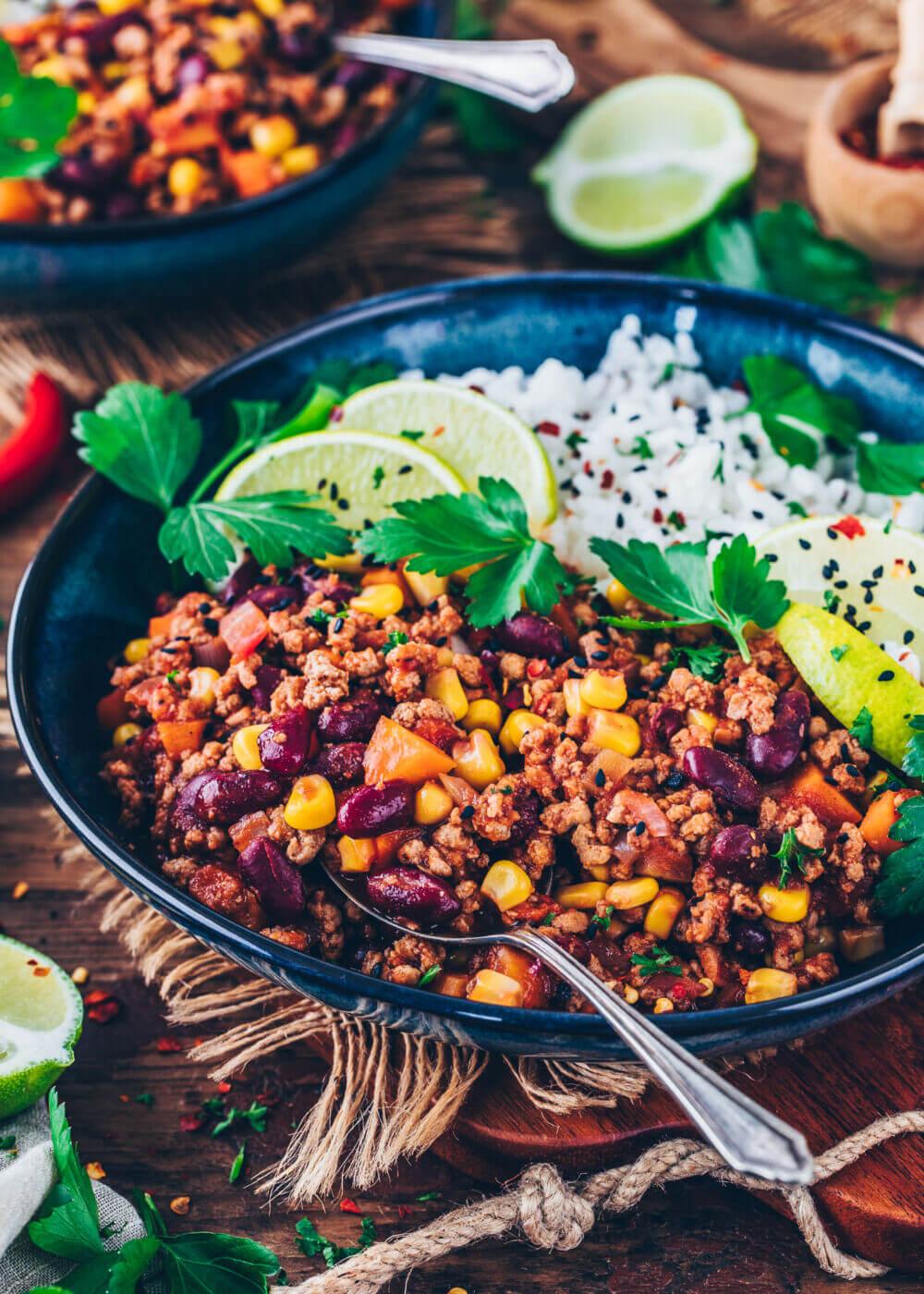 Veganes Chili sin carne mit Bohnen und Mais, serviert zu Reis, mit Sesam, Limetten und Petersilie dekoriert