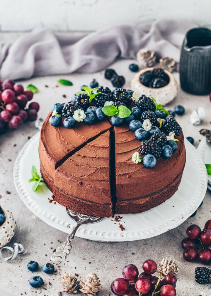 Veganer Schokoladenkuchen mit Frosting, Blaubeeren und Brombeeren