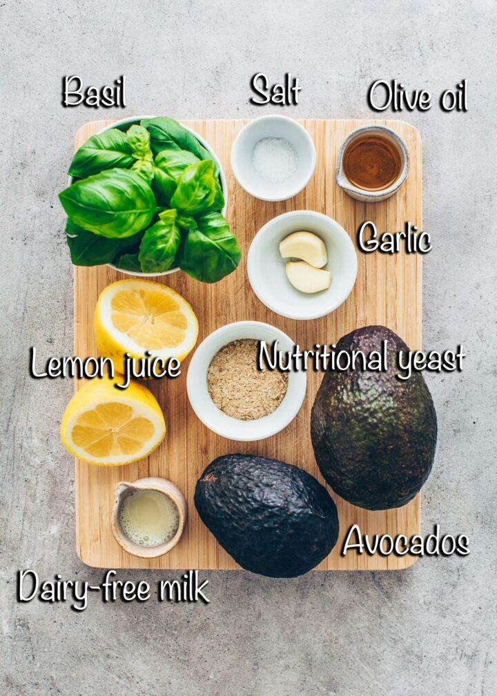Ingredients for guacamole (avocado, garlic, basil, lemon juice, nutritional yeast flakes, dairy-free milk, olive oil, salt