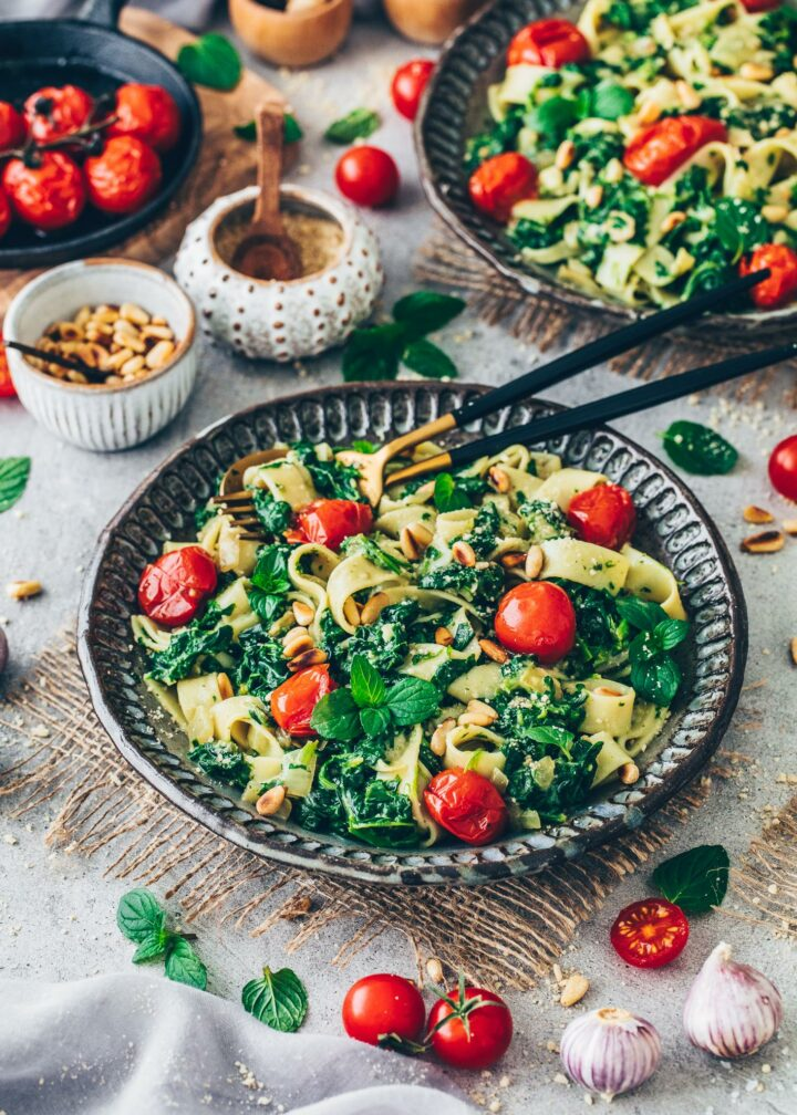 Creamy spinach pasta with roasted garlic tomatoes, vegan parmesan and pine nuts in a bowl