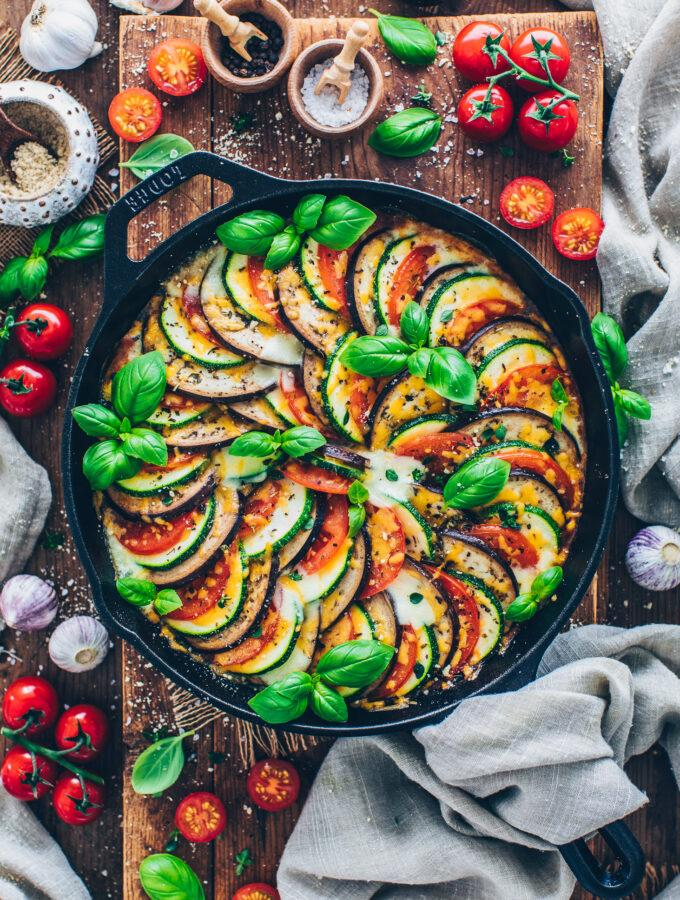 Ratatouille: thinly sliced eggplant, zucchini, and tomatoes in a skillet