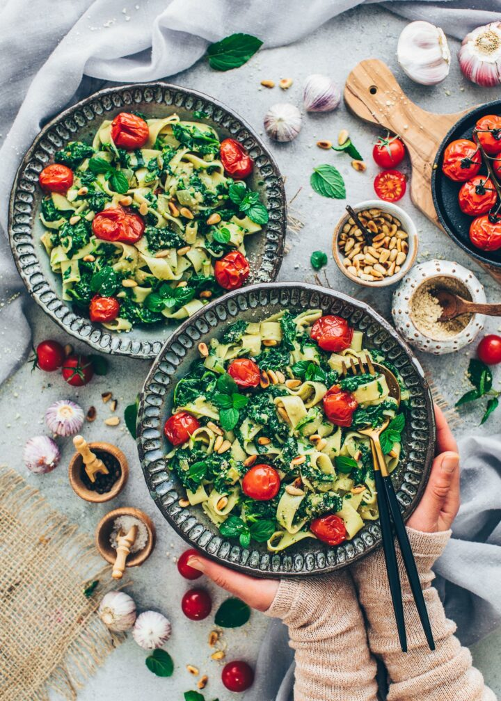 Creamy spinach pasta with tomatoes, vegan parmesan and pine nuts in bowls