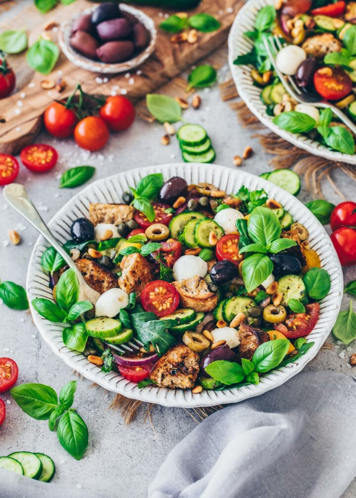 Panzanella with tomatoes, cucumber, bell pepper, bread, olives, mozzarella, arugula, pine nuts, red onions, capers, parsley, basil