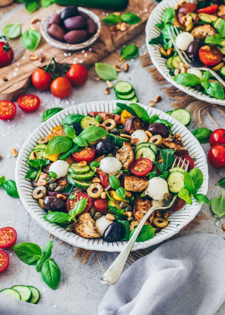 Bread Salad with tomatoes, cucumber, bell pepper, bread, olives, mozzarella, arugula, pine nuts, red onions, capers, parsley, basil