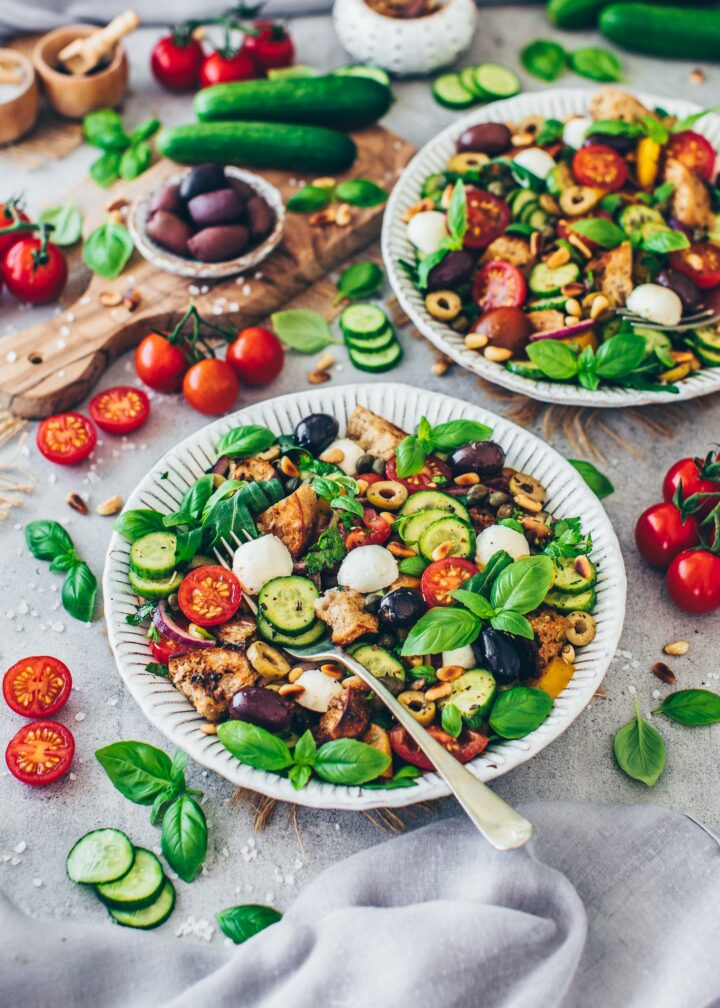 Italian Bread salad with tomatoes, cucumber, bell pepper, bread, olives, mozzarella, arugula, pine nuts, red onions, capers, parsley, basil (Panzanella)