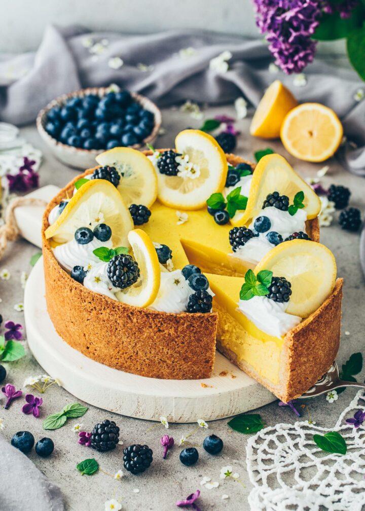 Lemon Cheesecake garnished with blueberries, blackberries, mint, and lemon slices