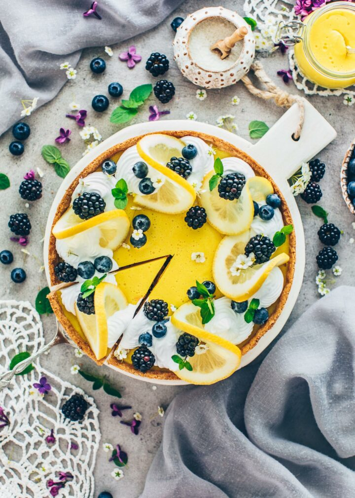 Zitronen-Käsekuchen mit Brombeeren, Blaubeeren, Zitronenscheiben und Minze dekoriert (Food Fotografie)