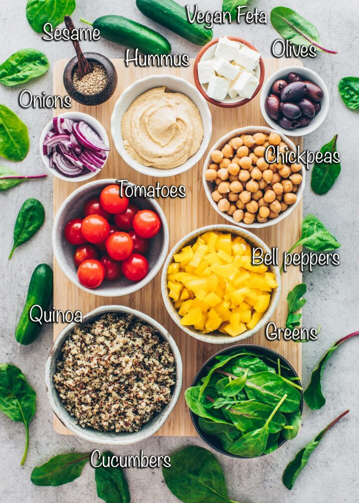 Buddha bowl ingredients: quinoa, greens, tomatoes, bell peppers, cucumber, chickpeas, hummus, vegan feta, olives, red onions, sesame