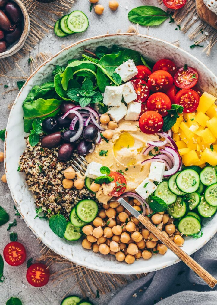 Mediterrane Buddha Bowl mit Quinoa, Tomaten, Salat, Paprika, Gurken, Oliven, Kichererbsen, Feta, Hummus