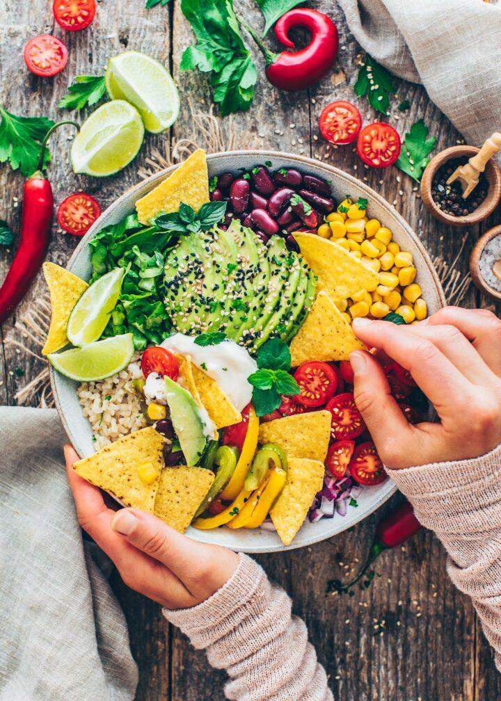 Tex-Mex Taco Bowl mit Fajita Paprika, Tomaten, Mais, Zwiebeln, Bohnen, Avocado, Salat, Sour Cream, Reis und Nachos