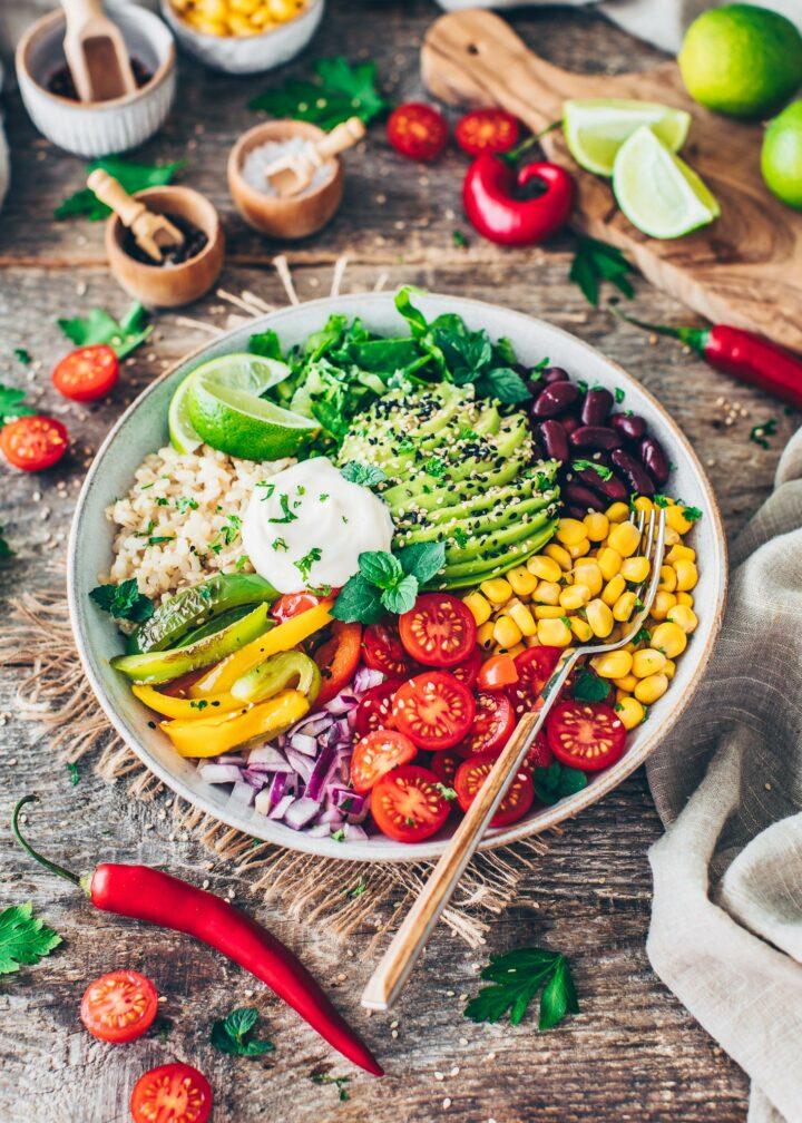 Burrito Bowl mit Fajita Paprika, Tomaten, Mais, Zwiebeln, Bohnen, Avocado, Salat, Mayonnaise und Reis