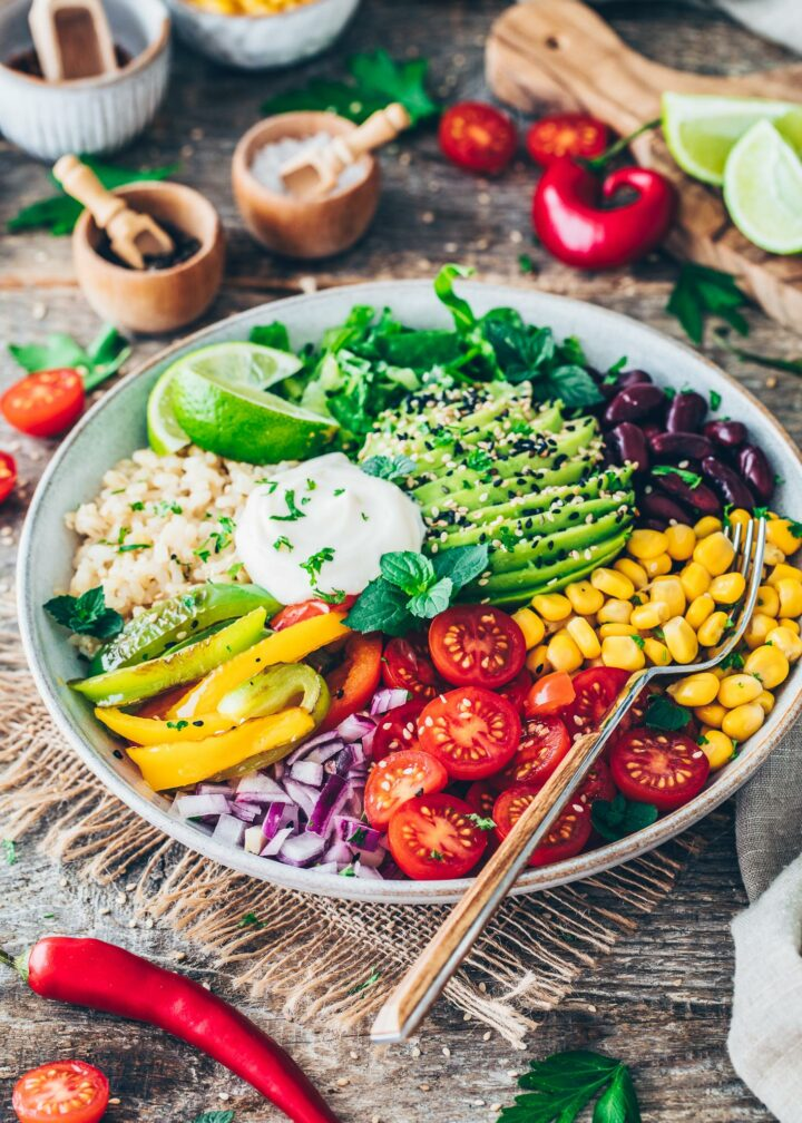 Mexikanische Buddha Bowl mit Fajita Paprika, Tomaten, Mais, Zwiebeln, Bohnen, Avocado, Salat, Mayonnaise und Reis