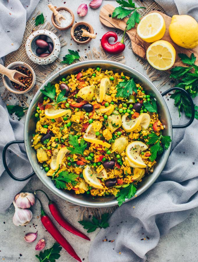 Vegan Paella with vegetables, crispy tofu, artichokes, and lemon slices