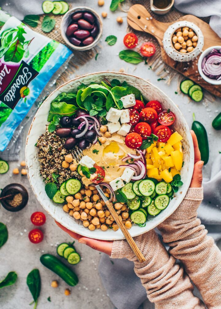 Salat Bowl mit Quinoa, Tomaten, Salat, Paprika, Gurken, Oliven, Kichererbsen, Zwiebeln, Tofu-Feta, Hummus