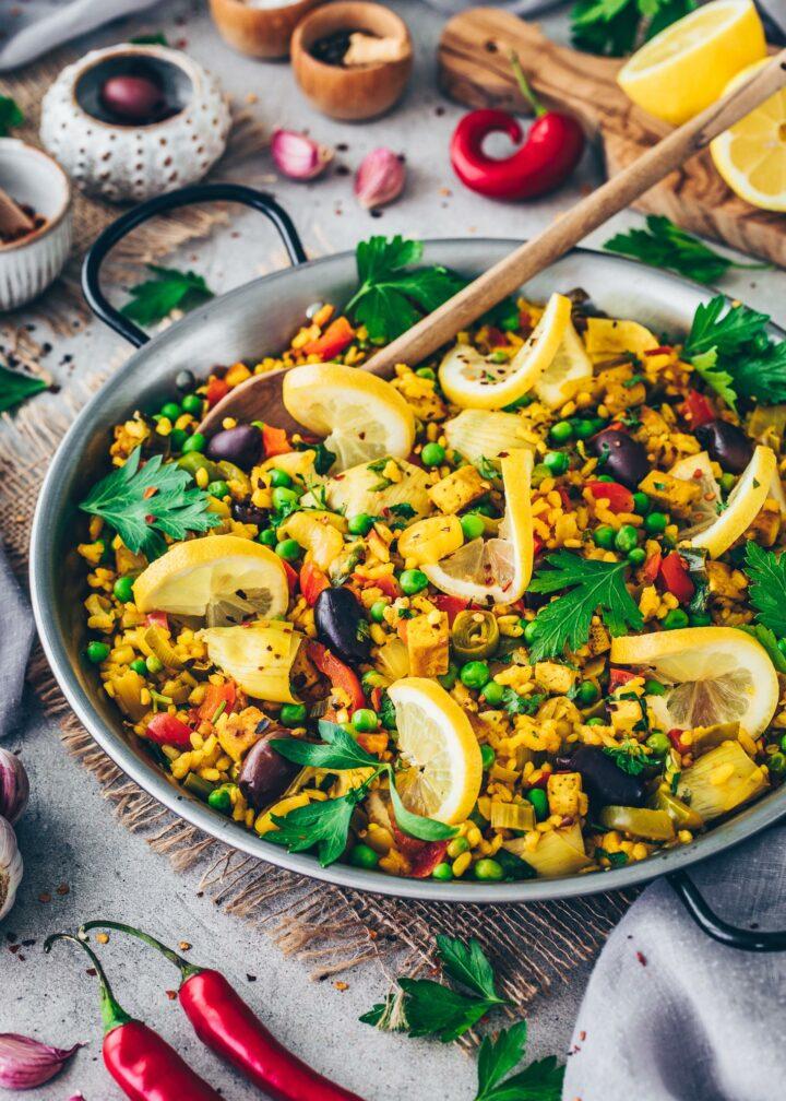 Vegane Paella mit Gemüse, Gemüse, Tofu, Artischocken und Oliven