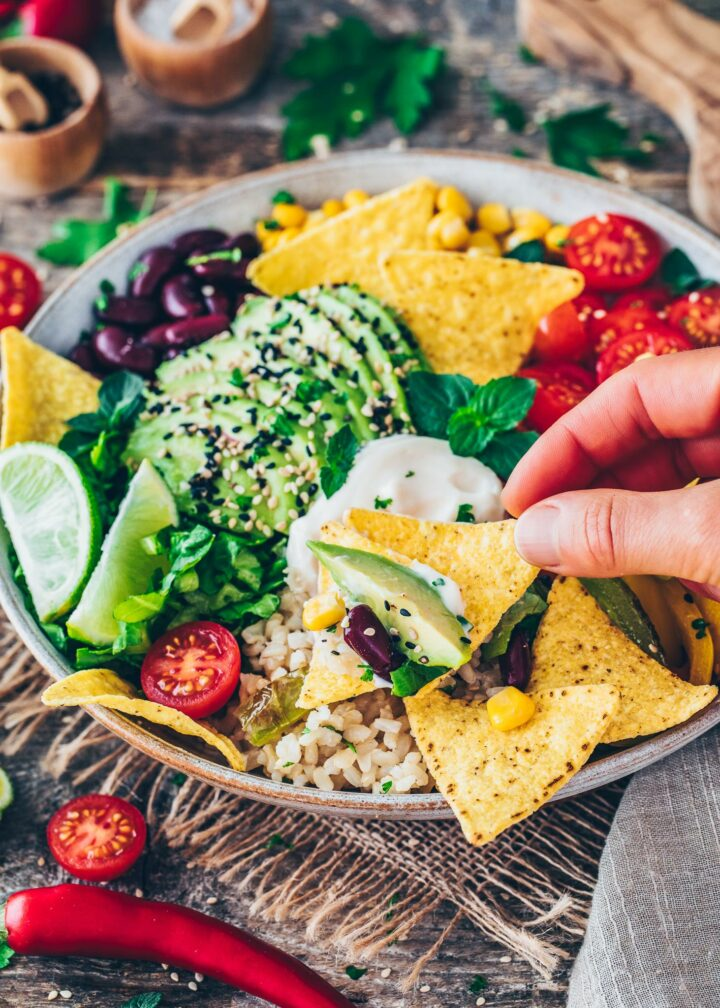 Mexikanische Taco Bowl mit Fajita Paprika, Tomaten, Mais, Zwiebeln, Bohnen, Avocado, Salat, Sour Cream, Reis und Nachos
