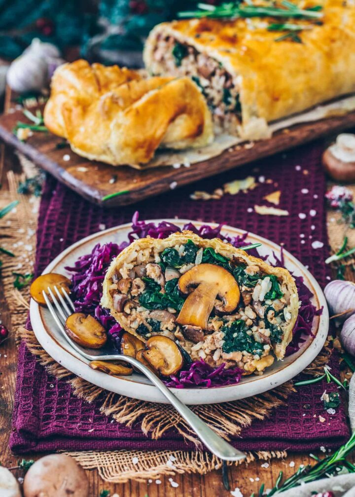 Vegan Wellington stuffed with mushrooms, rice and spinach, wrapped in puff pastry and served with gravy and red cabbage