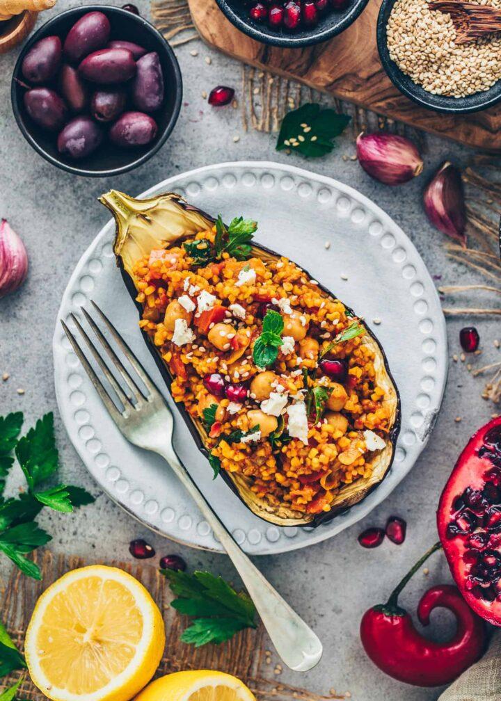 Auberginen mit Bulgur, Kichererbsen, Gemüse, veganem Feta, Granatapfelkernen, Oliven, Zitronen